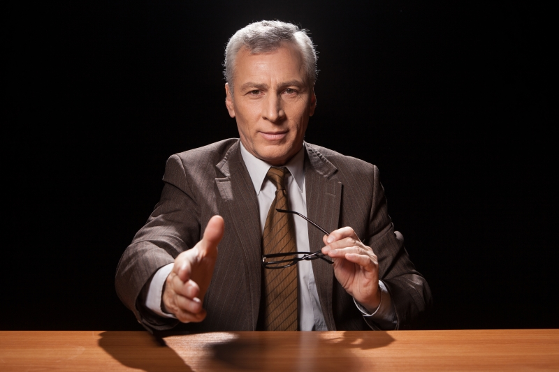 7914636-you-are-hired-cheerful-senior-man-in-formalwear-sitting-at-his-working-place-and-stretching-out-his-hand-for-shaking-while-isolated-on-black-background
